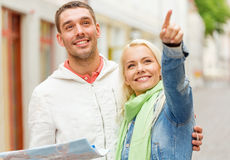 Happy couple with map exploring city Royalty Free Stock Images