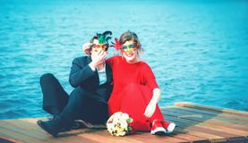 Happy Couple In Masquerade Masks Against A Turquoise Lake. Beautiful happy couple of lovers in masquerade masks - a men in a suit and a women in a red dress royalty free stock images