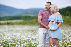 Happy couple on a meadow among the flowers Royalty Free Stock Images