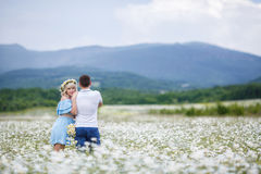 Happy couple on a meadow among the flowers Stock Images