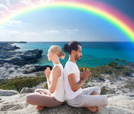 Happy couple meditating in lotus pose on beach Stock Image