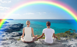 Happy couple meditating in lotus pose on beach Royalty Free Stock Image