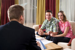 Happy couple meeting with agent at home Stock Image