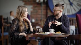 Happy couple meeting in coffee shop. Colleagues spending lunch break together considering their business. Male designer. Happy couple are having meeting in stock footage