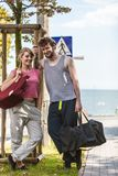 Happy couple man and woman with sport bags. Happy couple men and women with sport gym bags by sea ocean outdoor. Active young girl and guy in training suit Royalty Free Stock Image