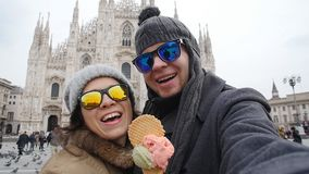 Happy Couple in Milan eating Ice cream taking selfie self-portrait photo on vacation travel in Italy. Winter vacation. Happy Young Couple in Milan eating Ice stock video footage