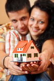 Happy couple with miniature house. Happy young couple offering a miniature house Royalty Free Stock Photography
