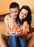 Happy couple with miniature house. Happy young couple offering a miniature house, boxes in the background Royalty Free Stock Images