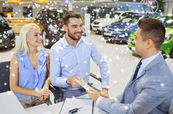 Happy couple with money buying car from dealer. Auto business, sale and people concept - happy couple with money buying car from dealer in auto show or salon Royalty Free Stock Images