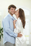 Happy couple in the morning. Happy couple embracing and kissing at home in the morning Stock Image