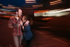 Happy couple in motion. Youth nightlife. Romantic date outdoors, blurred lights urban background. Cheerful hugging people, fun concept Royalty Free Stock Photography