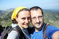 Happy couple in the mountains. Portrait of a happy couple taking selfie in the high mountains Stock Images