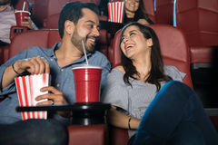 Happy couple at the movie theater. Attractive young couple having fun and enjoying the movie during a date at the cinema theater Royalty Free Stock Image