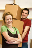 Happy couple moving - carrying boxes Stock Images