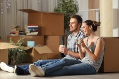 Happy couple moving home resting contemplating house stock images