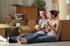 Happy couple moving home resting and talking stock image