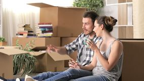 Happy couple moving home resting and talking stock video