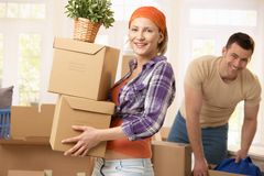 Happy couple moving house. Happy couple carrying boxes at moving house stock photo