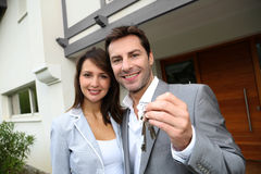 Happy couple moving in new house. Couple in front of new home holding door keys Royalty Free Stock Photo