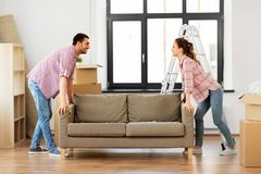 Happy couple moving sofa at new home stock photo