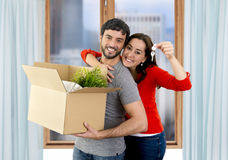Happy couple moving together in a new house unpacking cardboard boxes. Young happy Hispanic couple moving together in a new flat or apartment carrying cardboard Stock Images