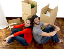 Happy couple moving together in a new house unpacking cardboard boxes. Young happy Hispanic couple moving together in a new house , flat or apartment unpacking Royalty Free Stock Photos