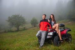 Happy couple near four-wheeler ATV in foggy nature Royalty Free Stock Image