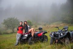 Happy couple near four-wheeler ATV in foggy nature Stock Photos