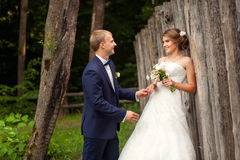 Happy couple near wooden fence in park Stock Photo