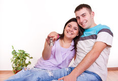 Happy couple in new apartment. Happy smiling young couple holding keys to their new apartment Stock Photo