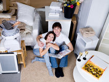 Happy couple in the new flat. Happy loving smiling couple sitting on the floor with photo album - high angle Royalty Free Stock Photos