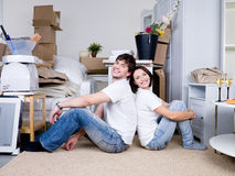 Happy couple in the new home. Smiling happy couple sitting back-to-back on the floor in the new home Royalty Free Stock Image