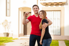 Happy couple with a new house. Good looking Hispanic young couple holding the keys to a house they just bought Stock Photo