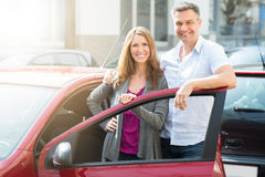 Happy Couple With New Red Car. Portrait Of Happy Couple Standing With Their Newly Purchased Red Car royalty free stock photo
