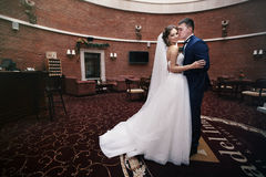 Happy couple of newlyweds hugging in luxury reception hall Stock Images