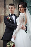 Happy couple of newlyweds hugging and posing in front of old chu. Rch door in Lviv Stock Photography