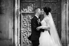 Happy couple of newlyweds kissing in front of old church door b& Royalty Free Stock Photo
