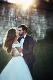 Happy couple of newlyweds kissing at sunset with castle wall bac Stock Image