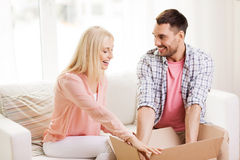 Happy couple with open parcel box at home Royalty Free Stock Images