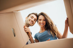 Happy couple opening a box. Smiling young couple opening a carton box and looking inside, relocation and unpacking concept Stock Images