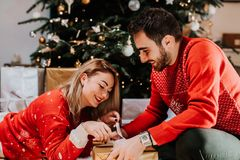 Happy couple opening a christmas present. Details of holidays royalty free stock photography
