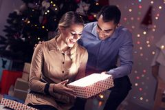 Happy Couple Opening Christmas Present. Picture Showing Happy Couple Opening Christmas Present Royalty Free Stock Images