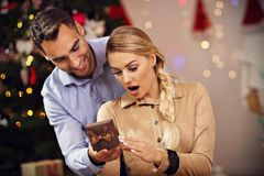 Happy Couple Opening Christmas Present Royalty Free Stock Photography
