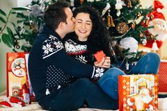 Happy couple opening christmas presents stock photo
