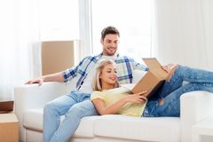 Happy couple opening parcel box at home. People, delivery, shipping and postal service concept - happy couple opening cardboard box or parcel at home royalty free stock image