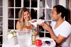 Happy Couple in Outdoor Cafe. A happy couple sharing a bottle of wine in an outdoor cafe in Europe royalty free stock image