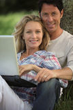 Happy couple outdoors. With laptop Stock Image