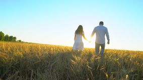 Happy couple outdoors having fun, walking on wheat field at sunset nature. romantic happy family in Love. Young man and