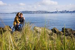 Happy Couple Outside. A cute young couple sitting outside on a beach in West Seattle Royalty Free Stock Image