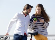 Happy couple outside looking at text message on cell phone. Close up portrait of a happy couple standing outside and looking at text message on cell phone royalty free stock images